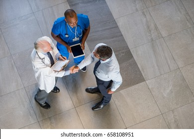 High angle view of senior doctor shaking hands to representative of pharmaceutical companies. Top view of businessman shaking hands with physician in a hospital. Man conclude an agreement with doctor.