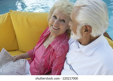 High angle view of a senior happy couple sitting together on sofa with swimming pool in the background