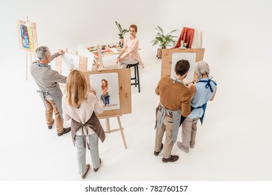 high angle view of senior people painting on easels during art class