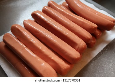 High angle view of several hot dogs on a white paper towel.