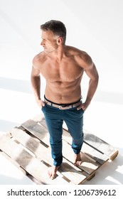 high angle view of shirtless handsome adult man standing on pallet on white and looking away