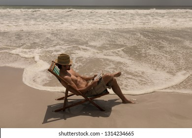 High angle view of shirtless young man with hat relaxing on sun lounger and using laptop on beach in the sunshine