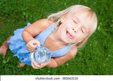 High angle view shot of blonde little girl wearing blue dress holding glass of water licking her lips with her eyes closed in a summer garden
