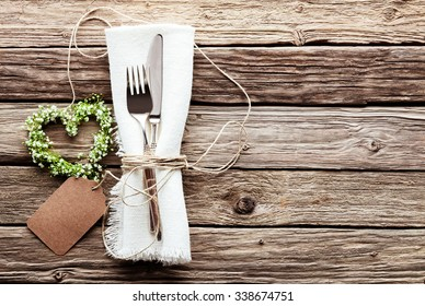 High Angle View of Small Heart Shaped Greenery Wedding Wreath at Table Setting with Silver Knife and Fork Tied with String to Fringed White Napkin with Blank Tag on Rustic Wooden Table Surface