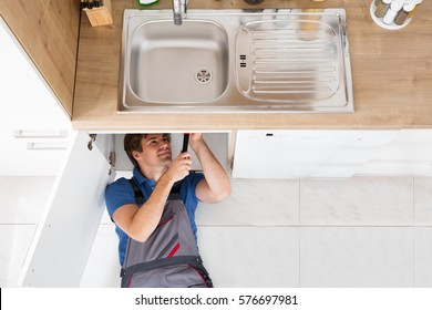 High Angle View Of Smiling Plumber Fixing Sink In Kitchen