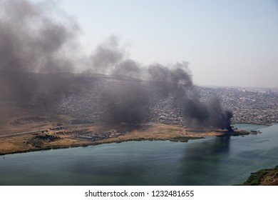 High angle view of smoke spreading from building. Arson of industrial warehouse, big smoke cloud spreading with wind. Massive damage on company building or warehouse engulfed in raging fire