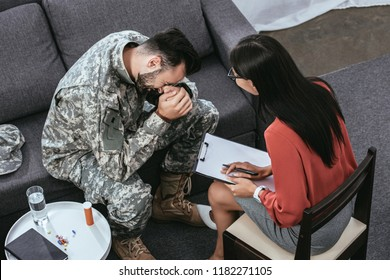 high angle view of soldier with ptsd crying at psychiatrists office during therapy