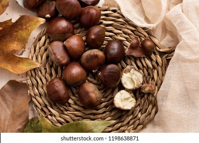 high angle view of some chestnuts out from a paper cone, on a rustic wicker mat, on a table next to some autumn leaves