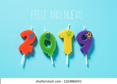 high angle view of some number-shaped candles of different colors forming the number 2019, and the text feliz ano nuevo, happy new year written in spanish, on a bright blue background