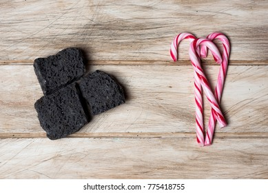high angle view of some pieces of candy coal and some candy canes on a rustic white wooden table