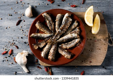 high angle view of some spanish grilled sardines in a brown earthenware plate, on a gray rustic wooden table sprinkled with some different spices, and some slices of lemon