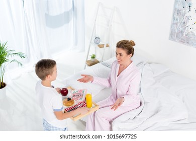 high angle view of son carrying breakfast for mother while she sitting on bed