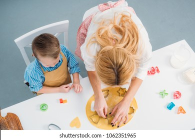 High angle view of son and mother using cooking molds