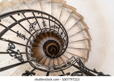 High angle view of spiral staircase with hand of man below.