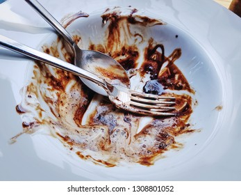High Angle View of  Spoon and Fork with Chocolate Leftovers on White Plate