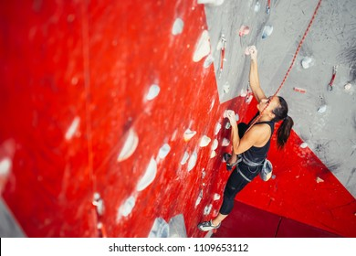High angle view of sporty brown-haired woman exercising wall climbing on colorful red artificial rock in climbing gym.