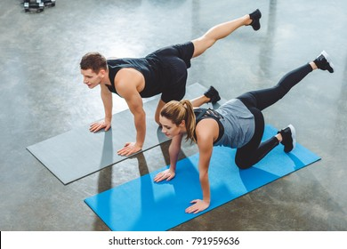 high angle view of sporty couple training on yoga mats in fitness studio