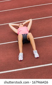 High angle view of a sporty woman suffering from headache on the running track