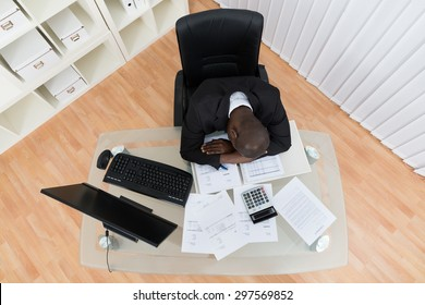 High Angle View Of Stressed Businessman Sleeping At Desk