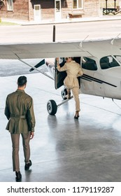 high angle view of stylish man walking while his girlfriend boarding in plane