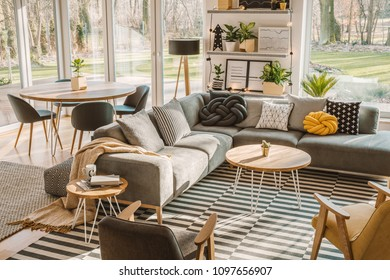 High angle view of a stylish, nordic living room interior with a wooden dining table, gray sofa and view on terrace and backyard. Real photo