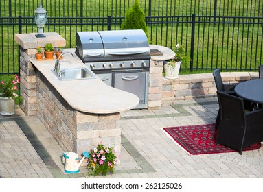 High angle view of a stylish outdoor kitchen on a brick patio with a built in gas barbecue,rug and dining table overlooking a green lawn and railing