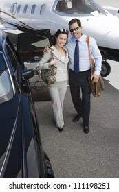 High angle view of a successful business couple standing together with arm around at airfield