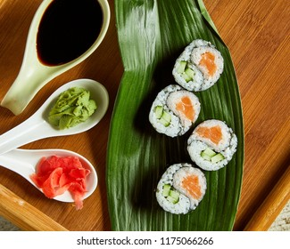 High angle view of sushi served on wooden plate and green leaf