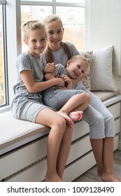High angle view of sweet happy Caucasian children siblings girl and boy playing tag at home, chasing each other in light spacious living room, being home alone. Childhood, joy, fun and happiness