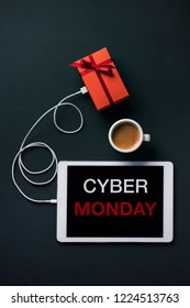 high angle view of a tablet with the text Cyber Monday in its screen, connected to a gift by a cable, and a cup of coffee, placed on a dark surface