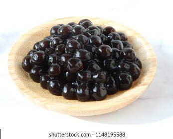 High angle view of tapioca ball (also known as boba in bubble tea) on wooden plate isolated on white background. Ingredients for making pearl milk tea and shaved ice at dessert shop. Food concept.