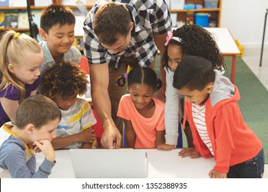 High angle view of a teacher learning at his school kids how using laptop in classroom at school