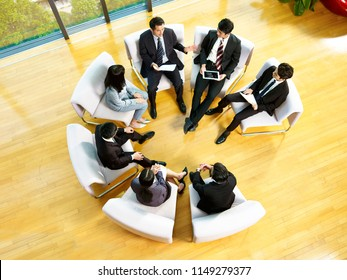 high angle view of team of asian business people sitting in a circle meeting in office.