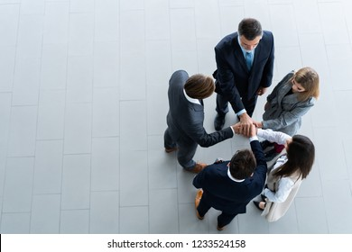 High angle view of a team of united coworkers standing with their hands together in a huddle in the modern office building