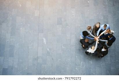 Hochwinkelaufnahme eines vereinten Teams von Geschäftsleuten, die in einer Hütte in der Lobby eines modernen Bürogebäudes mit ihren Händen stehen
