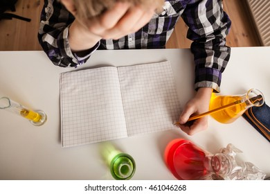 High Angle View of Teenage Boy Working on Chemistry Homework with Head in Hands and Sitting at Desk Surrounded by Beakers with Colorful Liquids