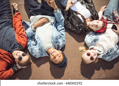 High angle view of teenagers group lying together and resting at skateboard park