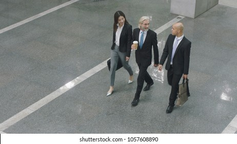 high angle view of three corporate executives talking while walking across lobby of modern office building.