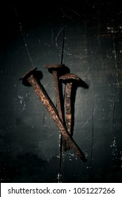 high angle view of three rusty nails, depicting the nails of the holy cross, on a rustic wooden surface, with a dramatic effect