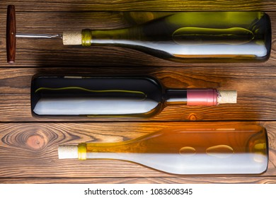 High angle view of three wine bottles lying against wooden background