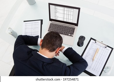 High angle view of tired businessman sleeping while calculating expenses at desk in office