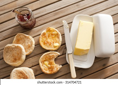 High Angle View of Toasted English Muffins with Butter and Jam on Top of Wooden Table