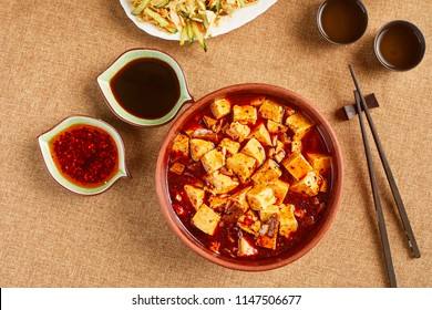 High angle view of tofu soup with chopstick sand sauces and two cups of tea. Chinese food