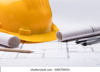 High Angle View Of Tools With Hardhat On Blueprint