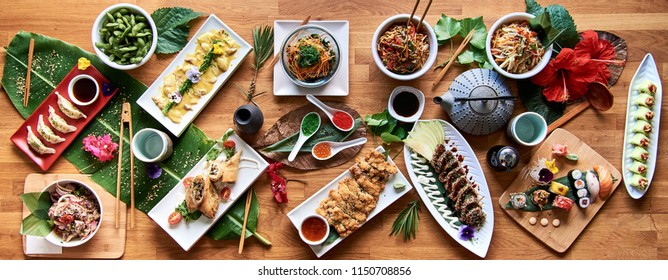High angle view of traditional Japanese food dishes served on the table. Set of sushi, rolls, spaghetti pasta, edamame and tuna tataki.
