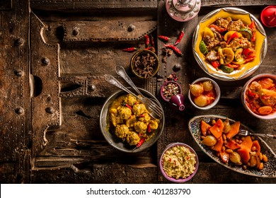 High Angle View of Traditional Tajine Dishes and Fresh Ingredients Arranged on Rustic Wooden Table Made from Old Door - Still Life with Copy Space