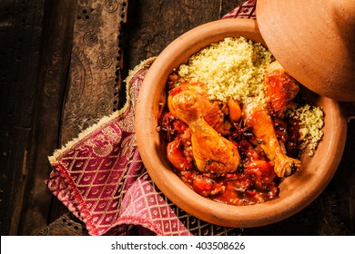 High Angle View of Traditional Tajine Berber Dish Made with Chicken Legs, Couscous and Savory Tomato Sauce Served in Covered Clay Pottery Dish on Decorative Wooden Table with Napkin
