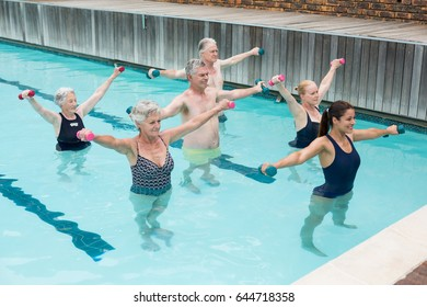 High angle view of trainer with senior people exercising in swimming pool