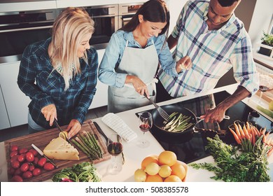 High angle view of trio cooking a meal with tomatoes, cheese, asparagus, fruit and other ingredients on kitchen counter and stove