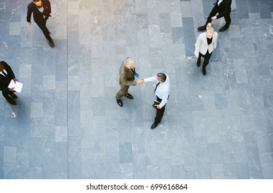 High angle view of two businessmen shaking hands together while colleagues walk around them in the lobby of a busy modern office building